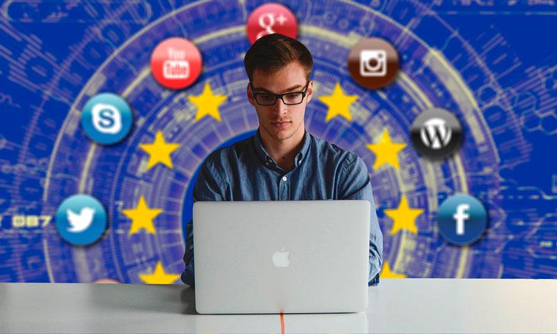 Fyr ved computer med tech logoer bag sig