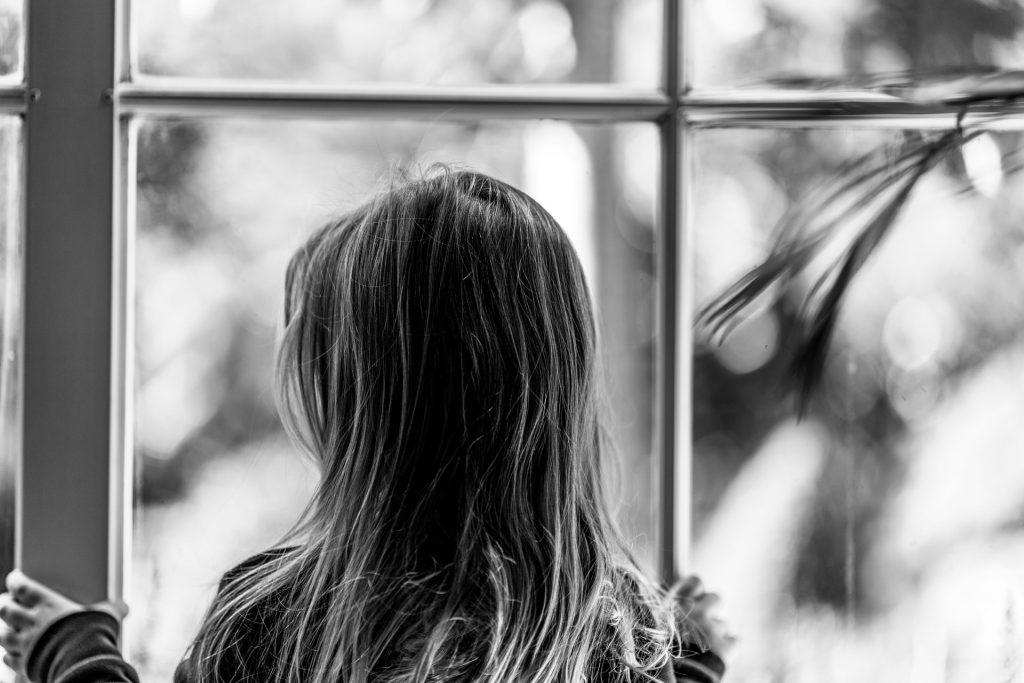 sort-hvid billede af pige, der kigger ud af vinduet
